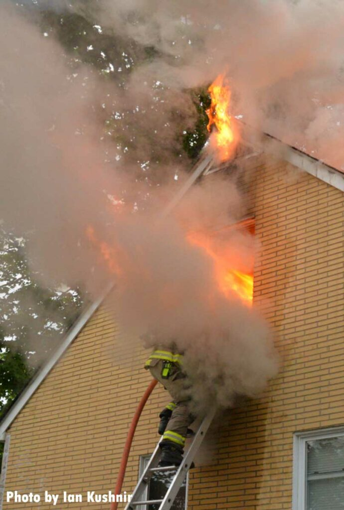 Flames roar from a window, obscuring a firefighter who has climbed a ladder
