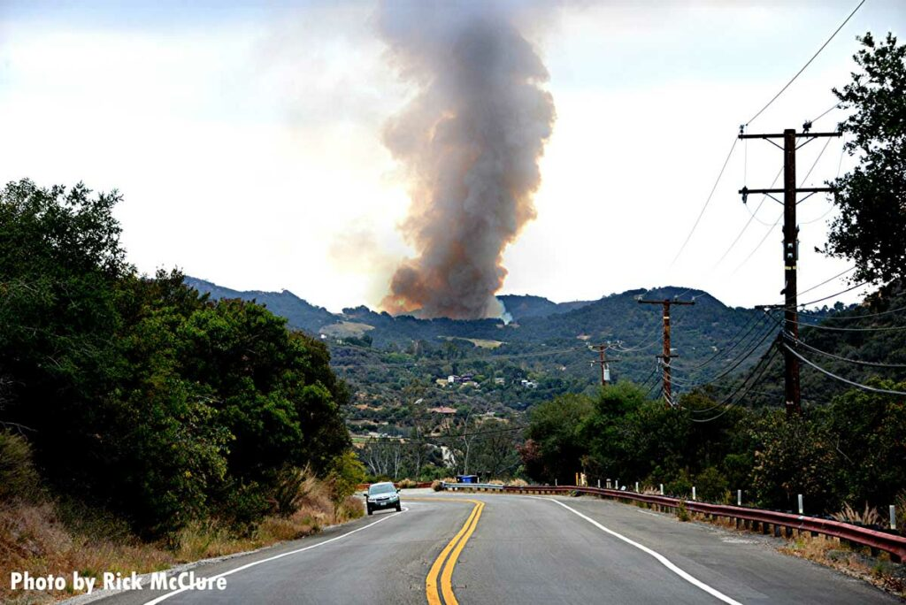Smoke rises from the Palisades fire, as seen from a roadway