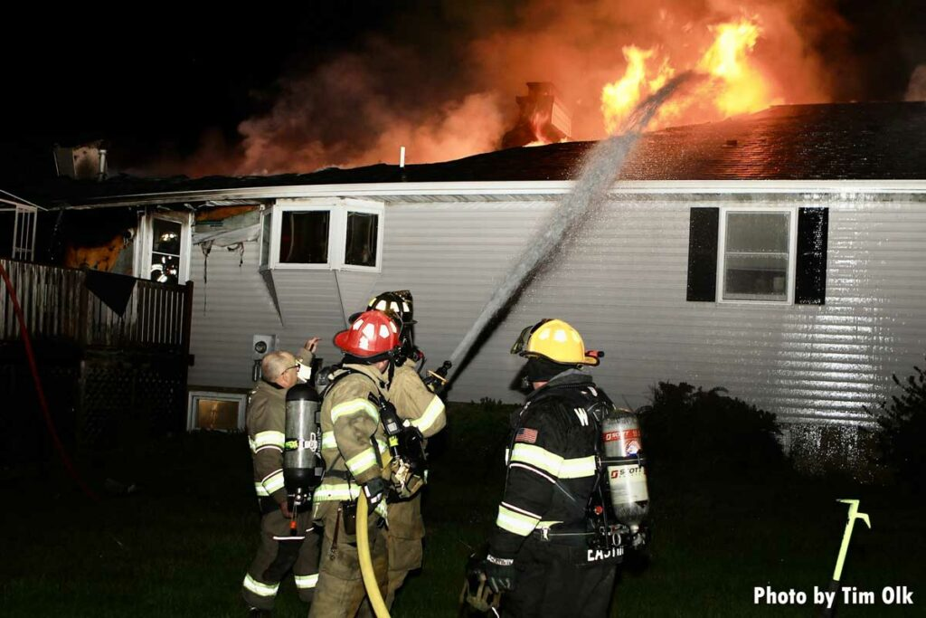 Firefighters train hosestream on flames emanating from roof at house fire in Danville, Iowa