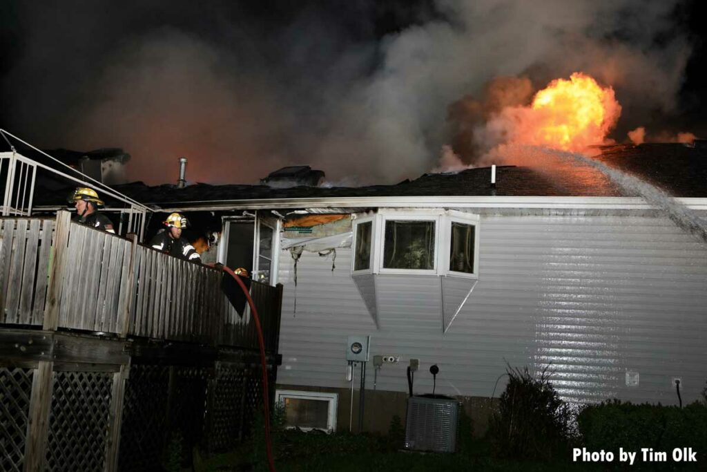 Flames roar from roof as exterior hosestream hits it