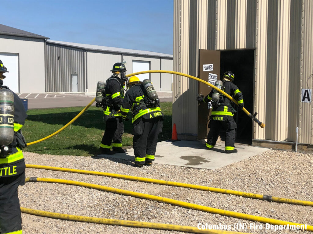 Firefighters stretch a line inside the training building