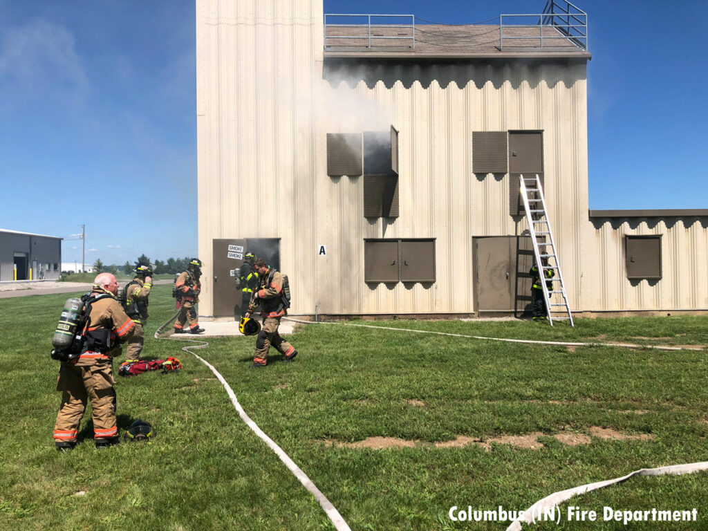 Smoke from the training building with a ladder thrown and firefighters with hoselines