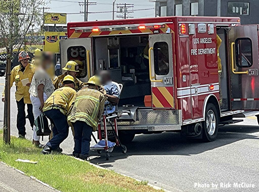 Firefighters load a patient into an ambulance