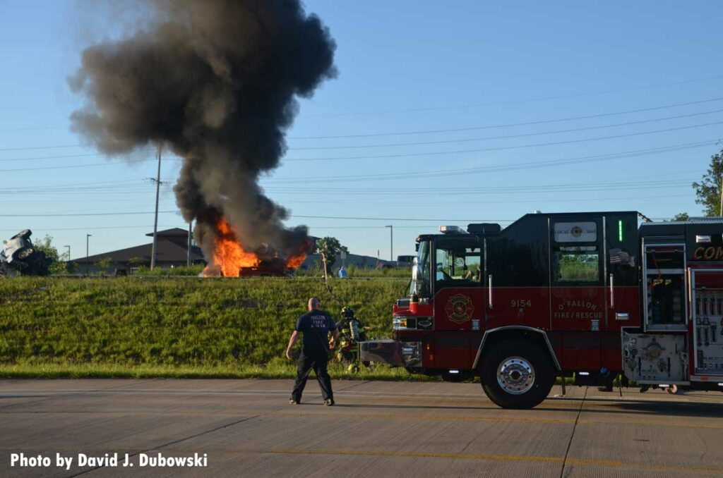 Firefighters confront a flaming vehicle and rising smoke