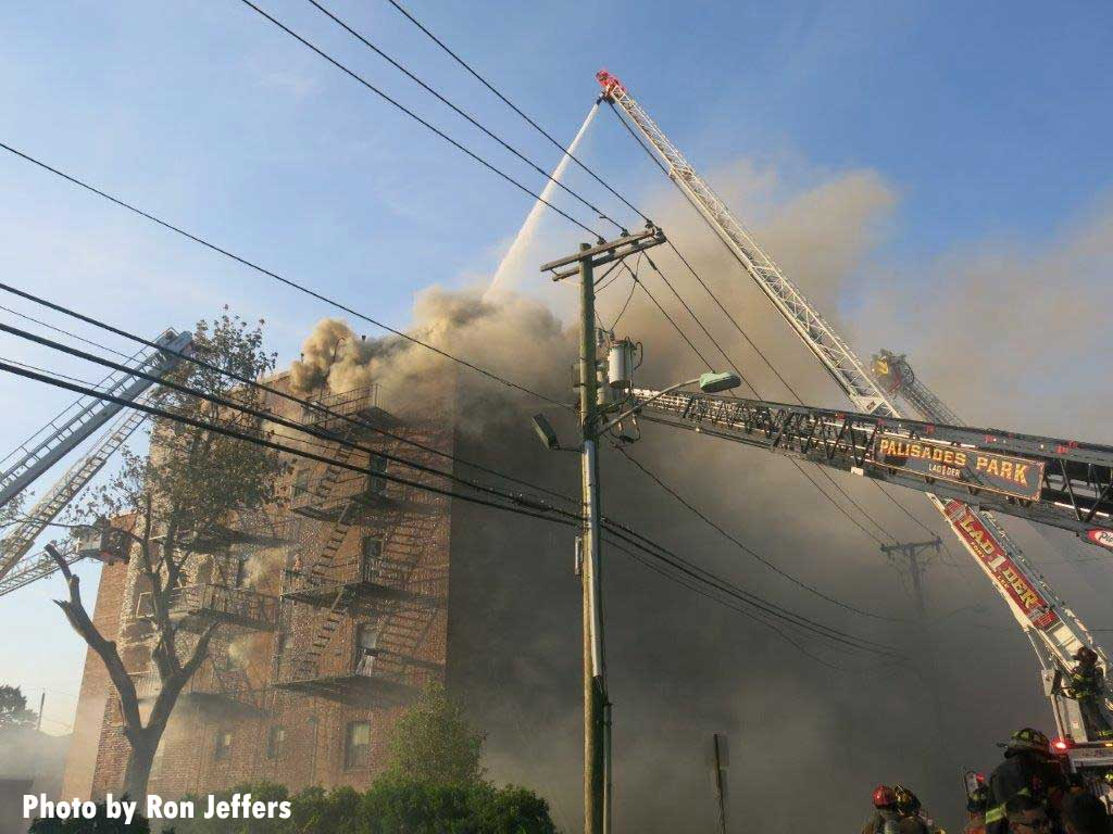 Smoke shoots from the top of a building in Fort Lee as multiple aerials from various fire departments are in use