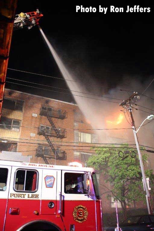Elevated master stream from Fort Lee rig putting water on flames