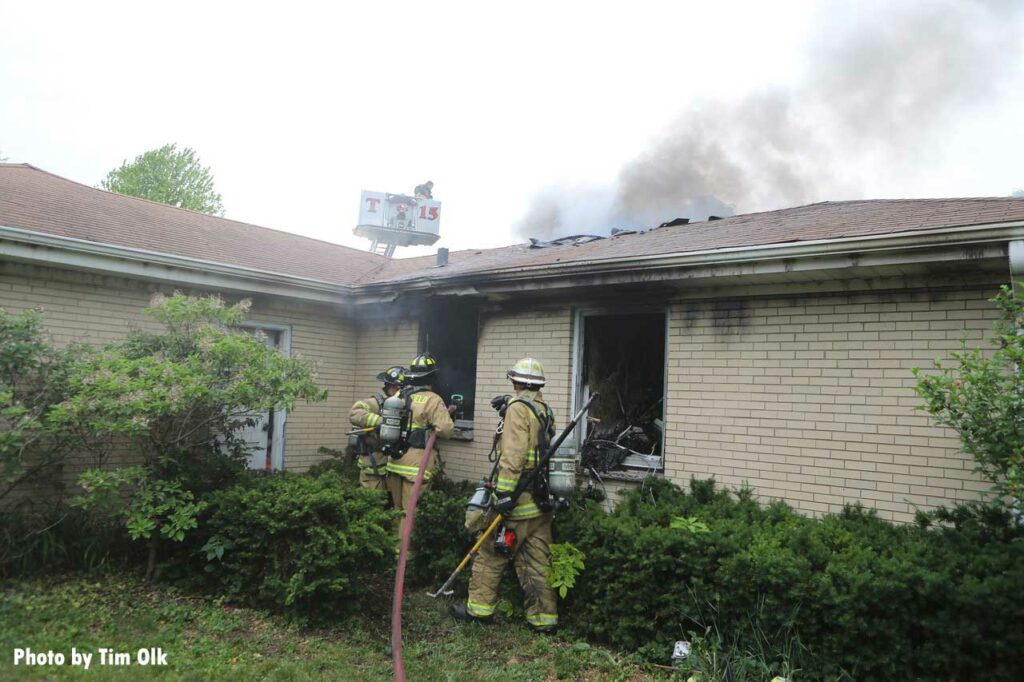 Firefighters put a hoseline through a window of the home