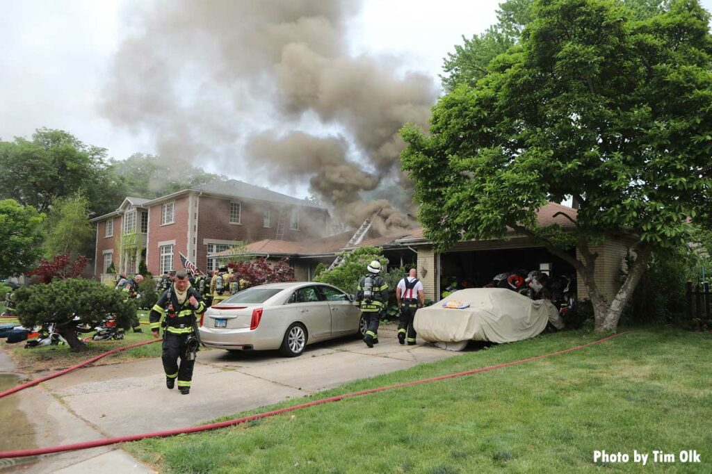 Two cars in the driveway of home with smoke showing and a ladder thrown on roof