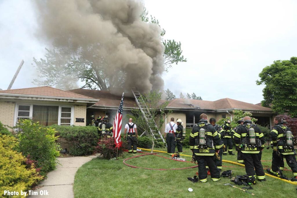 Firefighters in the yard at a ranch style home with a ladder and smoke showing