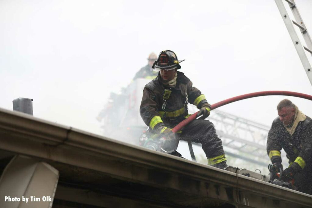 Firefighter on the roof puts a hoseline through the roof
