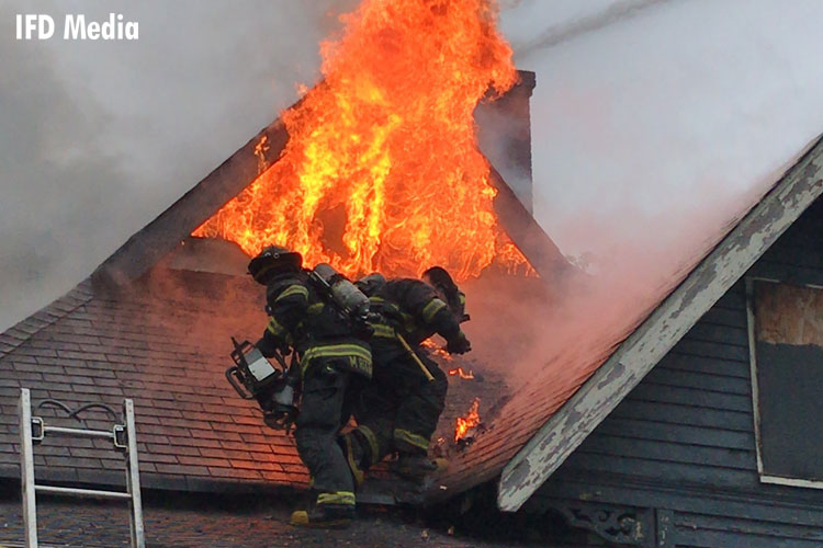 Firefighter on a roof with flames venting
